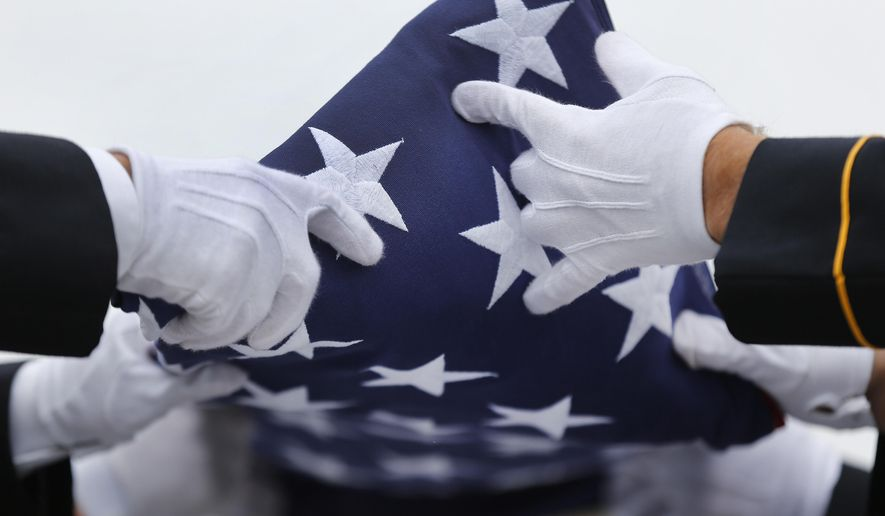 An Army honor guard folds a flag from a casket during a memorial service and burial at Great Lakes National Cemetery in Holly Township, Mich., Thursday, Sept. 11, 2014. (AP Photo/Paul Sancya) ** FILE **