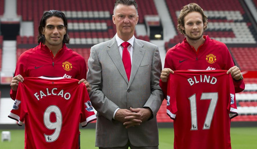 Manchester United's new players Radamel Falcao, left,  and Daley Blind, right, pose for photographs with manager Louis van Gaal at Old Trafford Stadium, Manchester, England, Thursday Sept. 11, 2014. The Colombian striker Falcao joined on a season-long loan deal from Ligue 1 side Monaco and Blind signed from Ajax as Louis van Gaal looks to bolster his attacking options. (AP Photo/Jon Super)