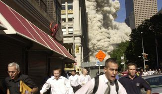 In this Sept. 11, 2001, file photo, people run from a collapsing World Trade Center tower in New York. (AP Photo/Suzanne Plunkett, File)