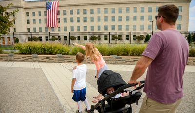 Heather Cichelli and her husband Ben bring their two sons Tyler, 8, and Harper of Mclean, Va., to the National Pentagon 9/11 Memorial on the 13th anniversary of the 9/11 attacks, Arlington, Va., Thursday, September 11, 2014. (Andrew Harnik/The Washington Times)