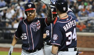 Washington Nationals' Adam LaRoche (25) is greeted at home plate by Bryce Harper (34) after hitting two-run home run off of New York Mets starting pitcher Bartolo Colon in the first inning of a baseball game Thursday, Sept. 11, 2014, in New York. (AP Photo/Kathy Kmonicek)