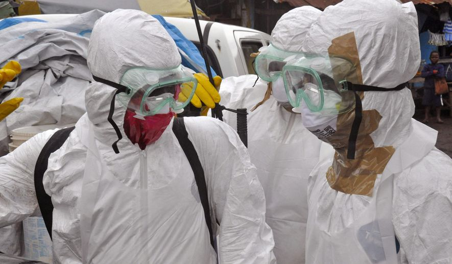 Health workers in protective gear leave after carrying the body of a woman that they suspect died from the Ebola virus, in an area known as Clara Town in Monrovia, Liberia, Wednesday, Sept. 10, 2014. A surge in Ebola infections in Liberia is driving a spiraling outbreak in West Africa that is increasingly putting health workers at risk as they struggle to treat an overwhelming number of patients. A higher proportion of health workers has been infected in this outbreak than in any previous one. (AP Photo/Abbas Dulleh)