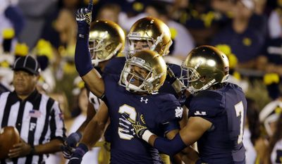 FILE - In this Sept. 6, 2014, file photo, Notre Dame wide receiver Amir Carlisle, center, celebrates a touchdown against Michigan during the first half of an NCAA college football game in South Bend, Ind. Carlisle says his faith kept him going through the hard times last season when his playing time dropped sharply after a nearly costly fumble against Purdue. (AP Photo/Michael Conroy, file)