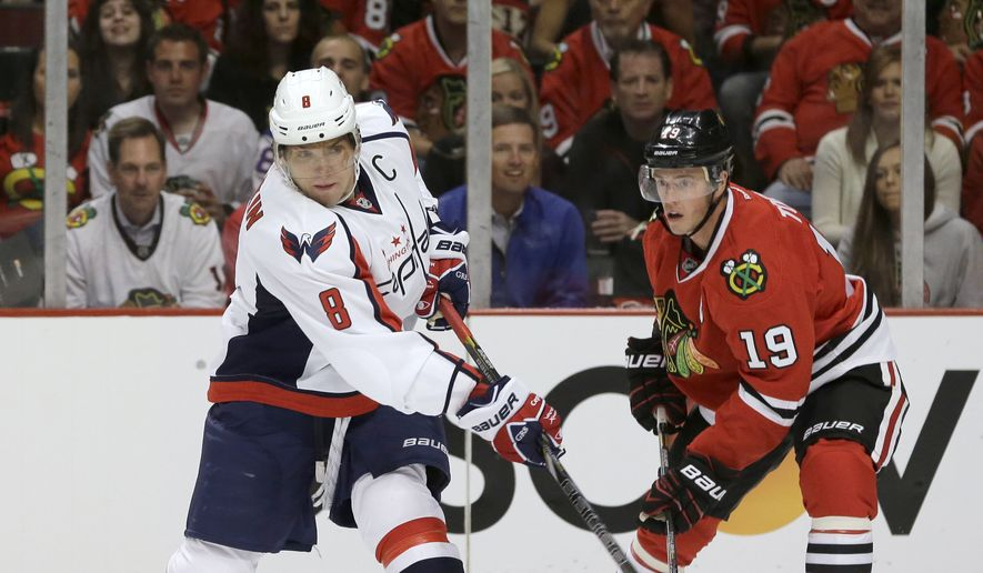 Washington Capitals right wing Alex Ovechkin (8) takes a shot past Chicago Blackhawks center Jonathan Toews (19) during the first period of an NHL hockey game Tuesday, Oct. 1, 2013, in Chicago. (AP Photo/Nam Y. Huh)