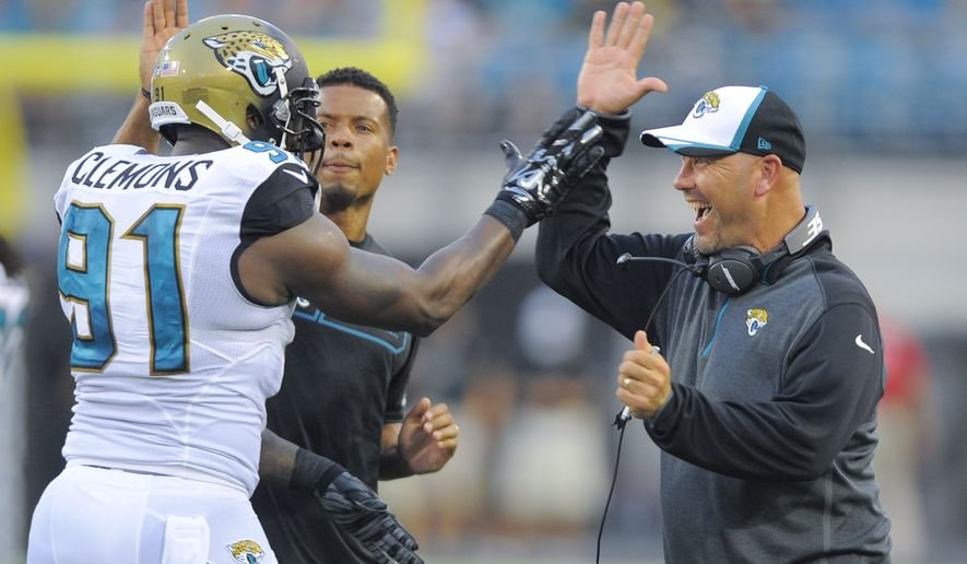 Jacksonville Jaguars head coach Gus Bradley, right, celebrates a big play with defensive end Chris Clemons (91) during the first half of an NFL preseason football game in Jacksonville, Fla., Friday, Aug. 8, 2014. (AP Photo/Stephen B. Morton)