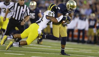 In this Sept. 6, 2014, photo, Michigan defensive back Delonte Hollowell, left, tackles Notre Dame wide receiver Amir Carlisle during the first half of an NCAA college football game in South Bend, Ind. Carlisle says his faith kept him going through the hard times last season when his playing time dropped sharply after a nearly costly fumble against Purdue. (AP Photo/Michael Conroy)