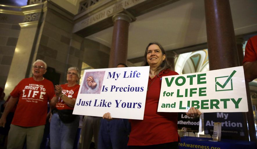 Joanne Schrader holds signs as she gathers with other abortion opponents in the rotunda of the Missouri Capitol Wednesday, Sept. 10, 2014, in Jefferson City, Mo. Missouri lawmakers will consider whether to override a veto by Gov. Jay Nixon of legislation requiring a 72-hour waiting period for abortions, one of the longest mandatory delays in the nation, during a special legislative session that begins Wednesday. (AP Photo/Jeff Roberson)
