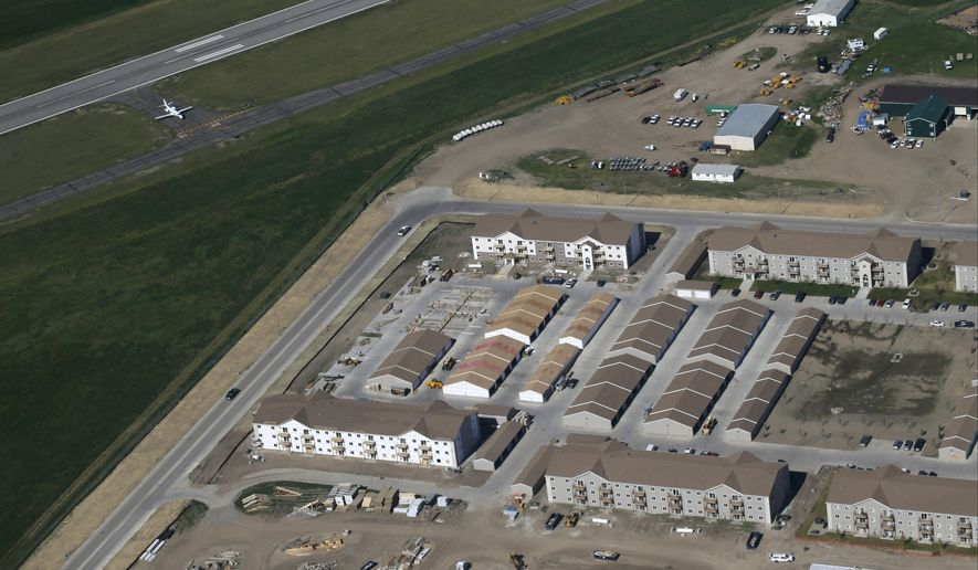 FILE - In this June 12, 2014 aerial file photo, various levels of housing construction can be seen near the Williston, N.D., airport. The city commission passed a record $250 million budget for 2015 for the oil boomtown of Williston on Tuesday, Sept. 9, 2014. The budget has grown rapidly in recent years to help the town cope with massive population growth resulting from booming oil production. Williston's population was just 14,716 in the 2010 census but tens of thousands of people have moved to the area since then. (AP Photo/Charles Rex Arbogast, File)