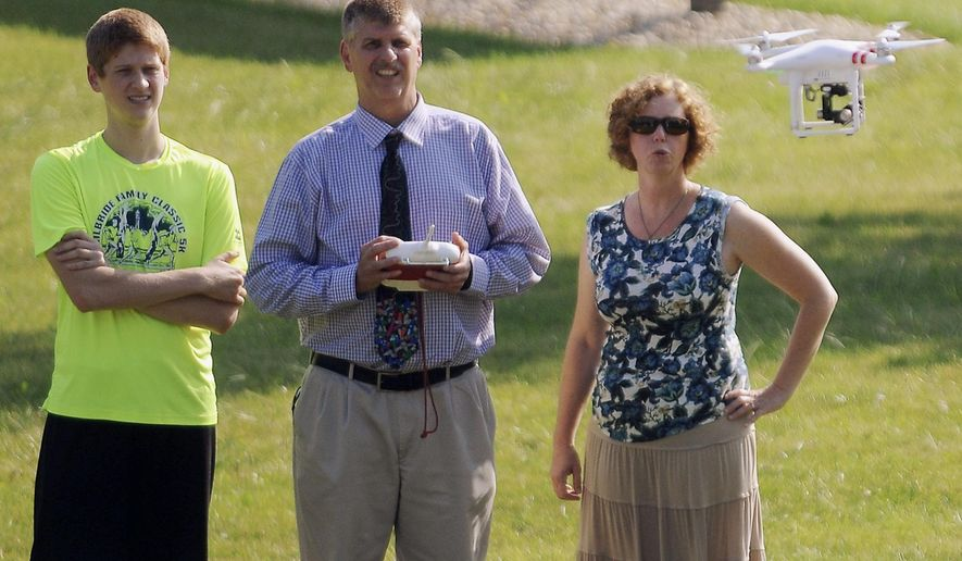 In this Aug. 26, 2014 photo, Noel LeVasseur Elementary School principal Jeff Gindy, center, operates the controls of a DJI Quad Copter, a remote-control drone that carries a GoPro camera, at the school in Bourbonnais, Ill. Also pictured and part of the drone program, are Jeff's son Cody, left, and Ann O'Gorman a teacher at the school. (AP Photo/The Daily Journal, Steve Anderson)
