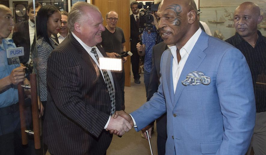 """Toronto Mayor Rob Ford, center, shakes hands with former heavyweight boxing champion Mike Tyson at City Hall in Toronto on Tuesday, Sept. 9, 2014. Tyson is in Toronto performing his one-man show """"Undisputed Truth"""" at the Air Canada Centre. (AP Photo/The Canadian Press, Darren Calabrese)"""