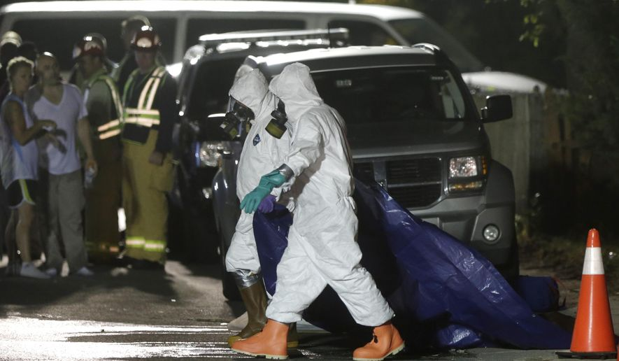 Investigators in protective clothing drag a tarp across the street in front of a house where a Massachusetts prosecutor said the bodies of three infants were found  Thursday, Sept. 11, 2014, in Blackstone, Mass. Worcester County District Attorney Joseph Early Jr. said Thursday authorities don't know when or how the babies died. (AP Photo/Steven Senne)