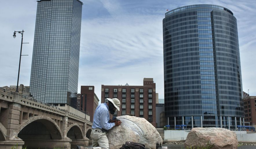 """In this photo taken on Sept.4, 2014, artist Kevin Sudeith works on his ArtPrize entry titled """"Grand River Fish Petroglyph"""" near the Grand Rapids Public Museum in Grand Rapids, Mich. Sudeith is carving images of the fish that navigate the river on rocks he has placed there.  (AP Photo/The Grand Rapids Press, Chris Clark) ALL LOCAL TELEVISION OUT; LOCAL TELEVISION INTERNET OUT"""