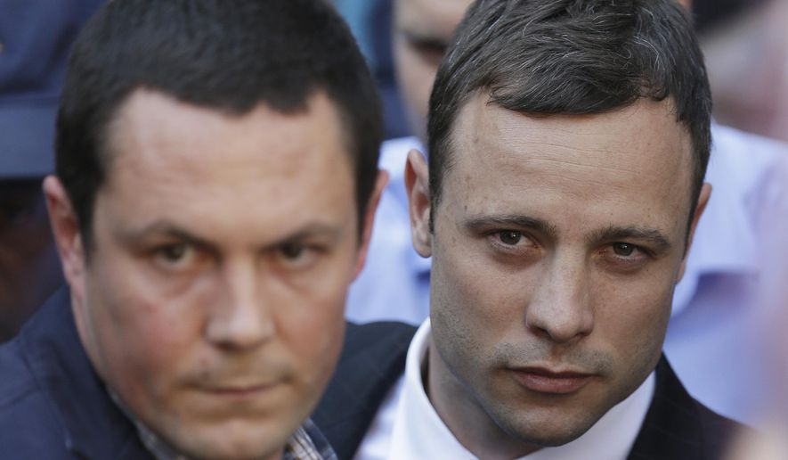 Oscar Pistorius, right, accompanied by a relative leaves the high court in Pretoria, South Africa, Thursday, Sept. 11, 2014. Presiding Judge Thokozile Masipa is expected to announce her verdict in Pistorius' murder trail after scrutinizing evidence Thursday and Friday given by 37 witnesses in a court transcript running to thousands of pages in a drama that has played out over six months. (AP Photo/Themba Hadebe)