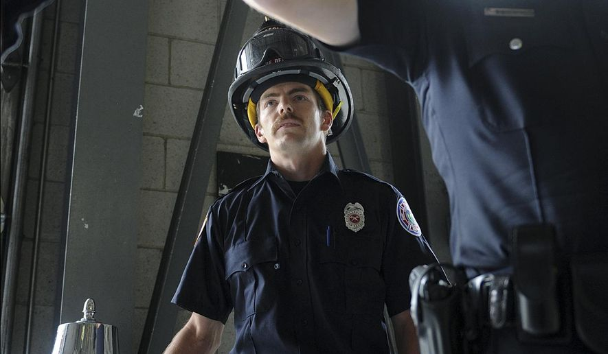 Firefighter Tim Millian, rear, rings the bell in honor of the fallen, as Police Officer Evan Rosenberg salutes during the town's annual 9/11 Memorial Ceremony, Wednesday, Sept. 11, 2014, in Wellesley, Mass. The two planes, hijacked by terrorists that crashed into New York's World Trade Center towers 13 years ago, departed from Logan International Airport in nearby Boston. (AP Photo/MetroWest Daily News, Kate Flock)