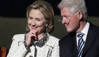 Then-Secretary of State Hillary Rodham Clinton, and former President Bill Clinton, listen to speakers in Washington in this Jan. 14, 2011, file photo. (AP Photo/Carolyn Kaster, File)