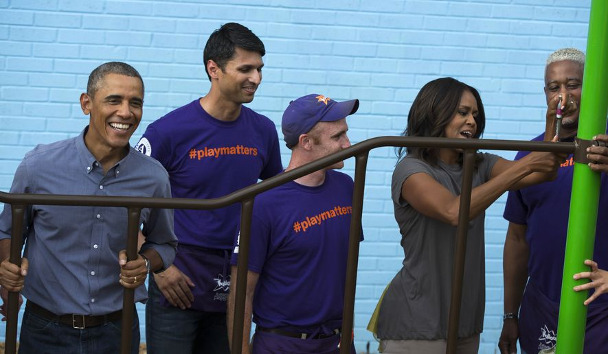 President Barack Obama, left, and first lady Michelle Obama, second from right, help build a playground as they participate in a service project at the Inspired Teaching School to mark the 13th anniversary of the 9/11 attacks, on Thursday, Sept. 11, 2014, in Washington. (AP Photo/Evan Vucci)