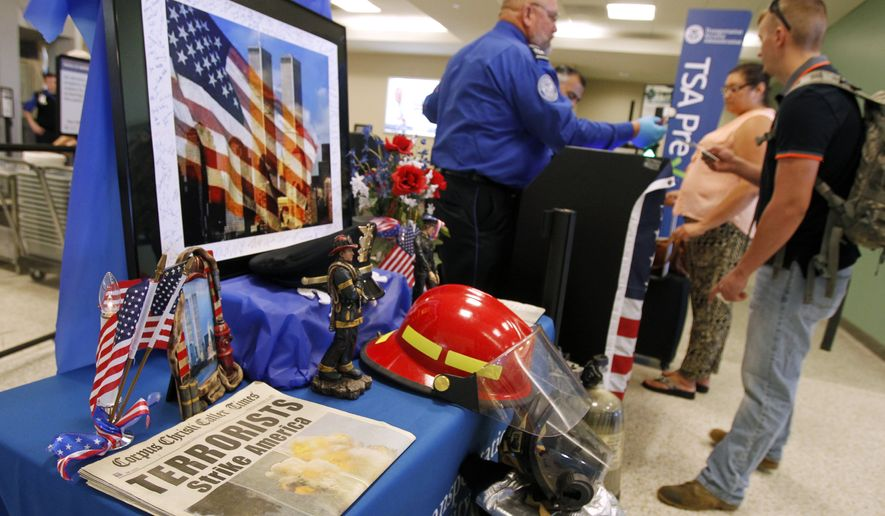 Airport passengers check in at the TSA checkpoint, where TSA officers set up a memorial honoring the victims of the Sept. 11, 2001 terrorist attacks, Thursday, Sept. 11, 2014, at the Corpus Christi International Airport in Corpus Chriti Texas. Thursday marks the 13th anniversary of the attacks. (AP Photo/Corpus Christi Caller-Times, Michael Zamora)  MANDATORY CREDIT; MAGS OUT; TV OUT