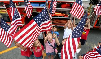 """Kindergarten students at Virginia Ave. Charlotte DeHart Elementary School in Winchester, Va. wave their American flags after a visit from area first responders that included an appearance by a fire truck during the """"Salute to Our Heroes"""" event at the school Thursday, Sept. 11, 2014, the 13th anniversary of the Sept. 11 attacks. (AP Photo, The Winchester Star, Jeff Taylor) ** FILE **"""