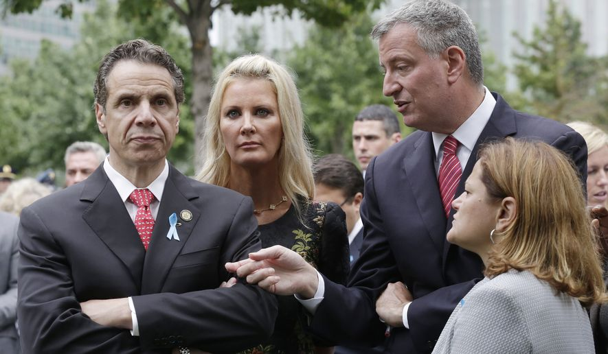 New York Governor Andrew Cuomo, left, listens to Mayor Bill de Blasio during memorial observances held at the site of the World Trade Center in New York, Thursday, Sept. 11, 2014. Joining them are Cuomo's partner Sandra Lee, second left, and Speaker of the New York City Council, Melissa Mark-Viverito, right.   Family and friends of those who died read the names of the nearly 3,000 people killed in New York, at the Pentagon and near Shanksville, Pennsylvania. (AP Photo/Mark Lennihan, Pool)