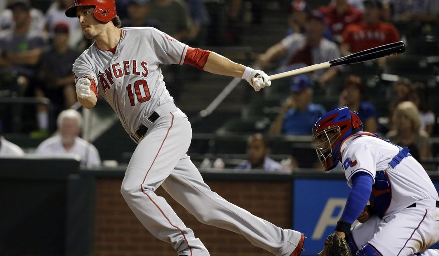 Los Angeles Angels' Grant Green (10) follows through on a two-run scoring single to left as Texas Rangers catcher Tomas Telis watches in the eighth inning of a baseball game, Thursday, Sept. 11, 2014, in Arlington, Texas. The hit scored Tony Campana and Erick Aybar. (AP Photo/Tony Gutierrez)