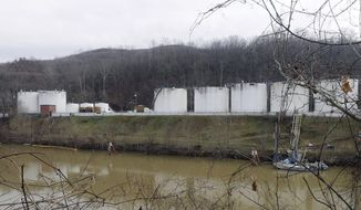 FILE - In this Jan. 13, 2014 file photo, workers, left, inspect an area outside a retaining wall around storage tanks where a chemical leaked into the Elk River at Freedom Industries storage facility in Charleston, W.Va. The powerful chemical industry is putting its lobbying muscle behind legislation that would establish standards for chemicals used in products from household goods to cellphones and plastic water bottles _ but also make it tougher for states to regulate them.   (AP Photo/Steve Helber, File)