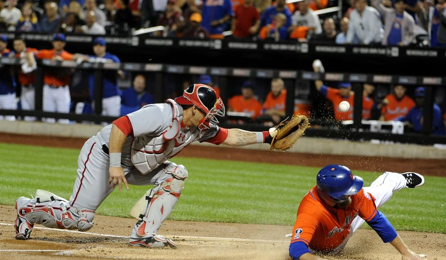 New York Mets' Lucas Duda arrives safely at home plate as Washington Nationals catcher Wilson Ramos drops the ball during the first inning of a baseball game Friday, Sept. 12, 2014, in New York. (AP Photo/Kathy Kmonicek)
