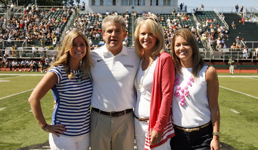 In this photo taken on Sept. 15, 2012 and released by Wagner College, Wagner football coach Walt Hameline, second from left, pose with his family, from left, daughter Kristin, wife Debi and daugher Kelly at a college football game against Monmouth in the Staten Island borough of New York. You think fall weddings are inconvenient for college football fans? Imagine being a coach with a daughter who has her heart set on a Saturday in late September. That was Hameline's dilemma, when his youngest daughter, Kelly, told him last fall the place she chose as the site of her big day had few dates available, and the one she picked was Sept. 20, the same day Wagner was scheduled to play Monmouth University. With the help of an old friend, Hameline was able to reschedule the game. (AP Photo/Wagner College, David Saffran)