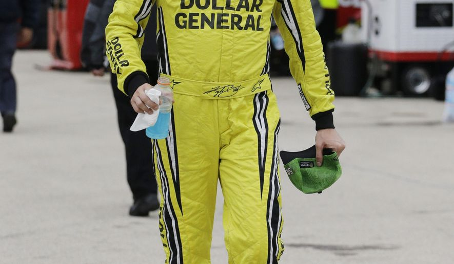 Driver Kyle Busch walks to his garage durin practice for the NASCAR Sprint Cup Series auto race at Chicagoland Speedway in Joliet, Ill., Friday, Sept. 12, 2014. (AP Photo/Nam Y. Huh)