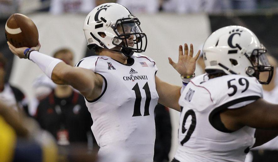 Cincinnati quarterback Gunner Kiel (11) throws a 22-yard touchdown pass in the first half of an NCAA college football game against Toledo, Friday, Sept. 12, 2014, in Cincinnati. (AP Photo/Al Behrman)