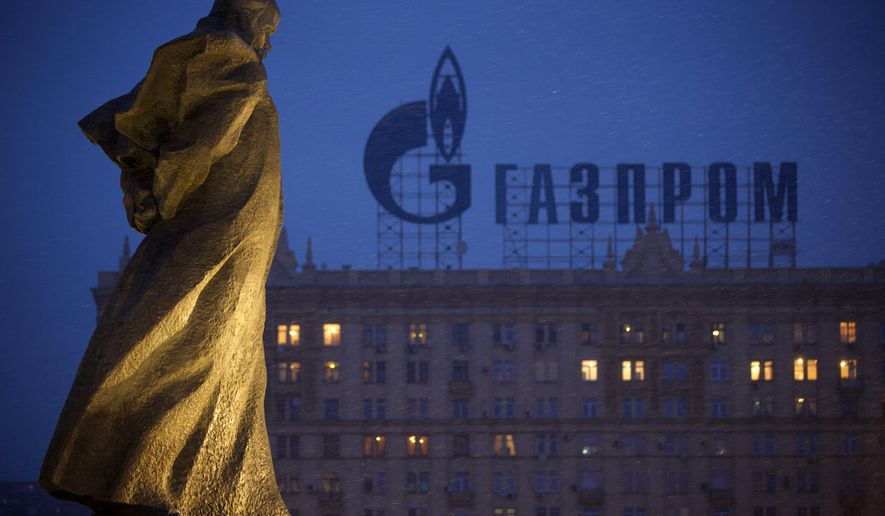 FILE - In this March 4, 2014 file photo, a monument to Ukrainian poet and writer Taras Shevchenko is silhouetted against an apartment building with a sign advertising Russia's natural gas giant Gazprom, in Moscow, Russia. Unsatisfied with a fragile cease-fire in Ukraine, the United States and the European Union levied new sanctions Friday against major Russian banks and defense companies, as well as penalties aimed at curtailing Russia's ability to develop oil and gas projects. But the restrictions on Russia's energy sector were carefully crafted to avoid impacting the country's current production of oil and gas, a move that would raise global energy prices at time of weak economic growth. Russia is the largest oil exporter outside of OPEC and the most important supplier of natural gas to Europe. (AP Photo/Alexander Zemlianichenko, file)