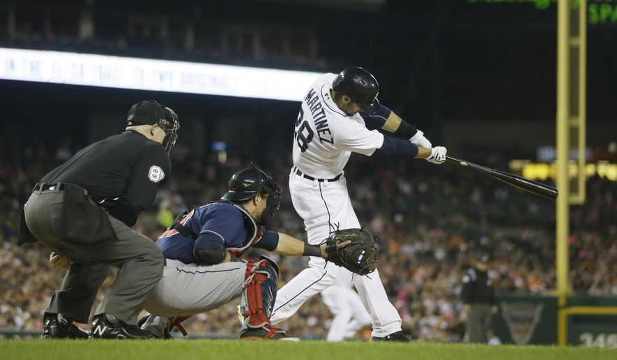 Detroit Tigers' J.D. Martinez, batting alongside Cleveland Indians catcher Yan Gomes and home plate umpire Mike Eastabrook, connects for a two-run triple during the seventh inning of a baseball game in Detroit, Friday, Sept. 12, 2014. (AP Photo/Carlos Osorio)