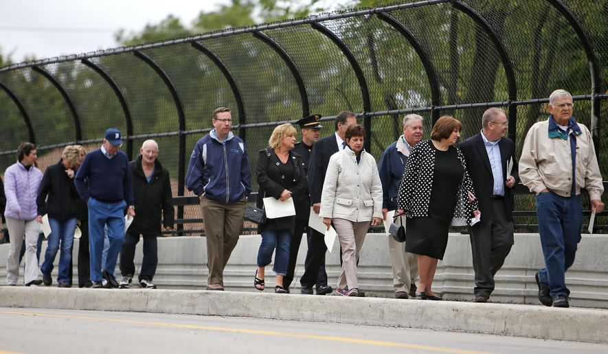 The Sign Unveiling Ceremony for James Bonneau has a bridge walk for those in attendance at the Officer James Bonneau Memorial Bridge in Jackson, Mich.,  Friday, Sept. 12, 2014.  (AP Photo/The Jackson Citizen Patriot, Danielle Duval)