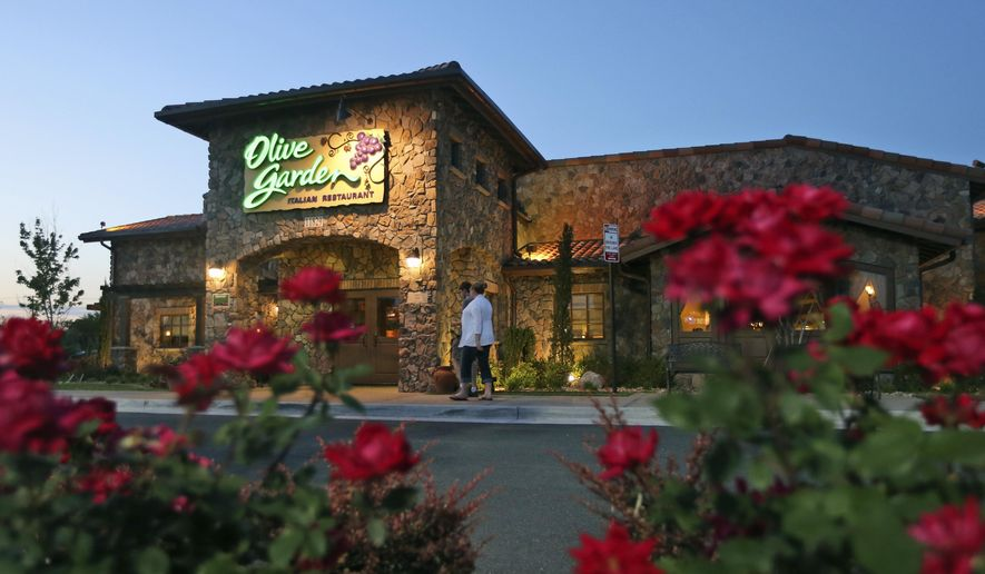 In this May 22, 2014 photo, patrons enter an Olive Garden Restaurant in Short Pump, Va. Olive Garden is hurting itself by piling on too many breadsticks, according to an investor that's disputing how the restaurant chain is run. (AP Photo/Steve Helber)