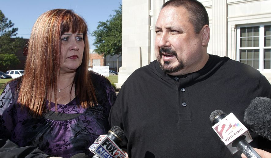 FILE - In this Monday, April 23, 2012 file photo, Faye Taylor, left, watches as Michael Taylor, right, answers questions for reporters following a scheduled hearing for murder suspect Kevin Sweat in Okemah, Okla. Faye Taylor and Michael Taylor are the step-mother and father of murder victim Ashley Taylor. The Taylors are are devising a potential law that would make it so workers are not penalized for attending court hearings of loved ones, especially when it has to deal with violent crimes. (AP Photo/Sue Ogrocki, File)