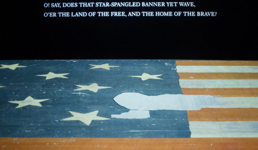 This photo taken Sept. 5, 2014 shows the Smithsonian's National Museum of American History in Washington exhibit of the flag that inspired the national anthem 'Star-Spangled Banner', with a portion of the flag that is missing a star and other section of fragments. Years ago parts of the flag were snipped off and handed out as mementos and the Smithsonian has been reacquiring some of those fragments and adding to their collection. (AP Photo/Pablo Martinez Monsivais)
