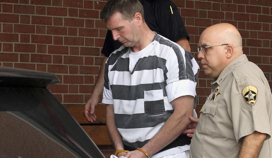 FILE - In this Aug. 28, 2014 file photo, Curtis Lovelace, 45, is escorted out of the Adams County Courthouse in Quincy, Ill., after being formally charged with first-degree murder in the February 2006 death of his first wife, 38-year-old Cory Lovelace. Lovelace, a former western Illinois prosecutor and University of Illinois football standout, is scheduled for an appearance related to the alleged suffocation Friday morning, Sept. 12, 2014, in Adams County Circuit Court. (AP Photo/The Quincy Herald-Whig, Steve Bohnstedt, File)