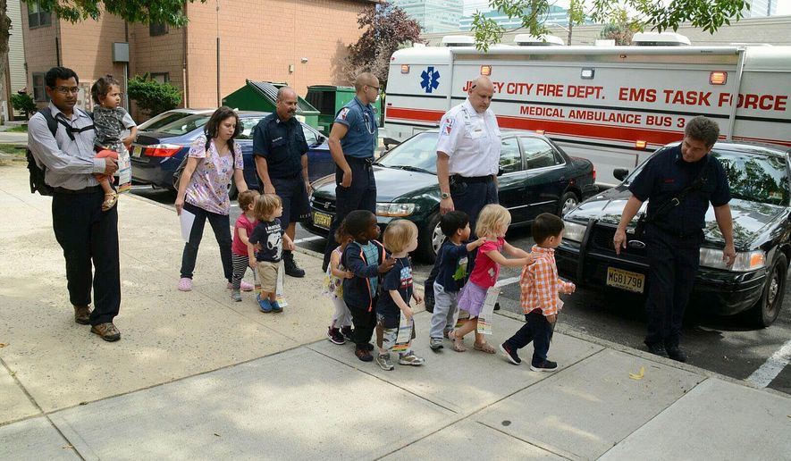 Children from the Growing Tree Learning Center II daycare center in Jersey City, N.J., who accidentally ingested a mixture of water and bleach are placed on an EMT bus to be brought to the Jersey City Medical Center on Thursday, Sept. 11, 2014. More than two dozen children and two adults accidentally drank a mixture of bleach and water at a day care center Thursday and were briefly hospitalized. (AP Photo/The Jersey Journal, Joe Shine)
