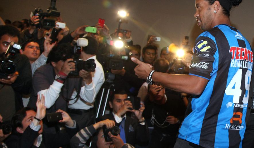 Brazil's Ronaldinho poses for a photo wearing his new Queretaro soccer club jersey at a press conference in Mexico City, Friday, Sept. 12, 2014. Mexican first-division club Queretaro signed the former 34-year-old soccer star, who had been without a club since leaving Brazil's Atletico Mineiro in July and had been negotiating with several clubs. The two-time FIFA world player of the year helped Atletico Mineiro win last year's Copa Libertadores for the first time. (AP Photo/Marco Ugarte)