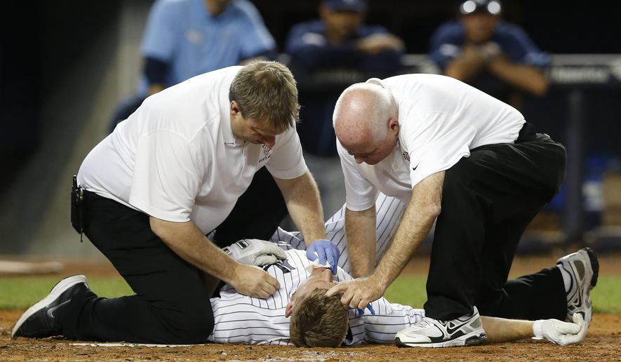 New York Yankees head trainer Steve Donohue, right, and his assistant, treat New York Yankees designated hitter Chase Headley (12) after he was hit in the head by a pitch thrown by Tampa Bay Rays relief pitcher Jake McGee in the ninth inning of a baseball game at Yankee Stadium in New York, Thursday, Sept. 11, 2014. Headley was replaced by a pinch runner. (AP Photo/Kathy Willens)