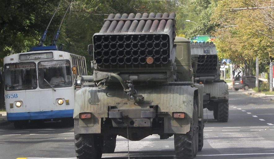 """Pro-Russian rebels drive multiple rocket launchers """"Grad"""" (means """"hail"""") in the town of Donetsk, eastern Ukraine, Thursday, Sept. 11, 2014. Two volleys of rocket fire rang out in Ukraine's eastern, rebel-held city of Donetsk, underscoring the difficulties of enforcing a cease-fire almost a week after it was signed. The city council of Donetsk confirmed in a statement Thursday there had been multiple explosions during the morning, but reported no casualties. ( AP Photo)"""