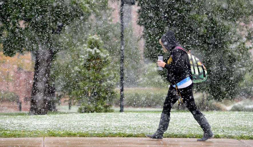 A pedestrian walks near the University of Colorado campus during the first snow of the season on Friday, Sept. 12, 2014, in Boulder. It's still summer, but in parts of Wyoming, South Dakota, Montana and Colorado, a blanket of snow covering green grass and flower gardens provided a preview of what is to come. (AP Photo/The Daily Camera, Cliff Grassmick) ** FILE **