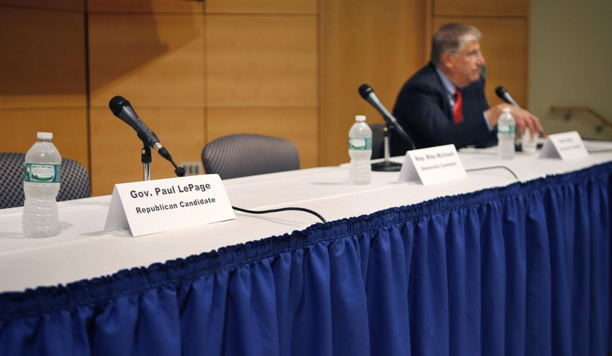 A seat at a table reserved for Gov. Paul LePage remains vacant after the governor decided to pull out of an energy forum at the University of Southern Maine, Friday, Sept. 12, 2014, in Portland, Maine. The Republican governor objected to the format for the event when he learned he would have to share the stage with the other gubernatorial candidates including independent Eliot Cutler, right. (AP Photo/Robert F. Bukaty)