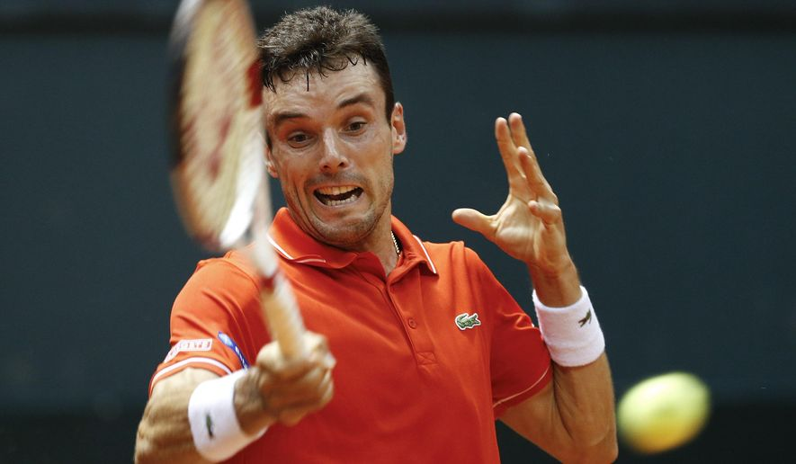 Roberto Bautista Agut of Spain returns the ball to Rogerio Dutra Silva of Brazil during their single tennis match of the Davis Cup World Group playoff in Sao Paulo, Brazil, Friday, Sept. 12, 2014. (AP Photo/Andre Penner)