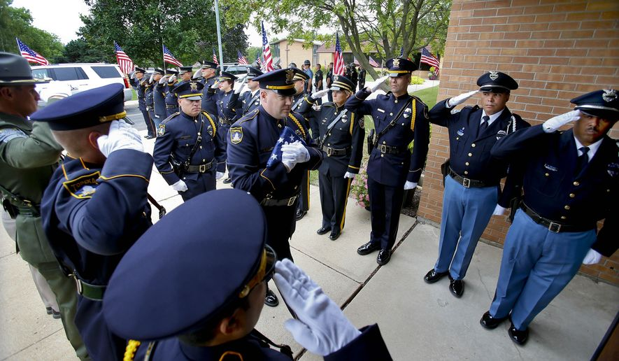 Topeka police officer Jeremy Warren carries the United States Honor flag inside the Countryside United Methodist Church in Topeka, Kan. on Thursday Sept. 11, 2014, where it will rest on the right side Topeka Police officer Cpl. Jason Harwood until his funeral on Saturday Sept. 13, 2014. Cpl. Harwood was killed in the line of duty during a traffic stop on Sunday Sept. 7, 2014. (AP Photo/The Topeka Capital Journal, Chris Neal)