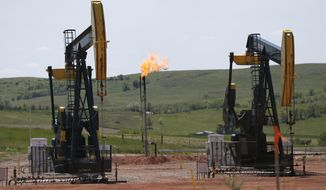 FILE -In this June 12, 2014 file photo, oil pumps and natural gas burn off in Watford City, N.D. The North Dakota Industrial Commission said North Dakota's oil production of 1,110,642 barrels of oil per day in July is a new record for the state. July's natural gas flaring rate dropped to 26 percent. The flaring rate was 28 percent in June. (AP Photo/Charles Rex Arbogast, File)