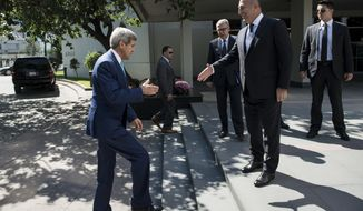 US Secretary of State John Kerry, left, shakes hand with Turkey's foreign minister Mevlut Cavusoglu upon his arrival at the Ministry of Foreign Affairs in Ankara, Turkey, Friday, Sept. 12, 2014. Kerry is in the region to speak with leaders about strategies to address the threat from the Islamic State, a militant extremist group. John Kerry said that the US would provide an additional $500 million in humanitarian aid to victims of the war in Syria, bringing total American assistance to $2.9 billion since the start of the conflict in 2011. (AP Photo/Brendan Smialowski, Pool)
