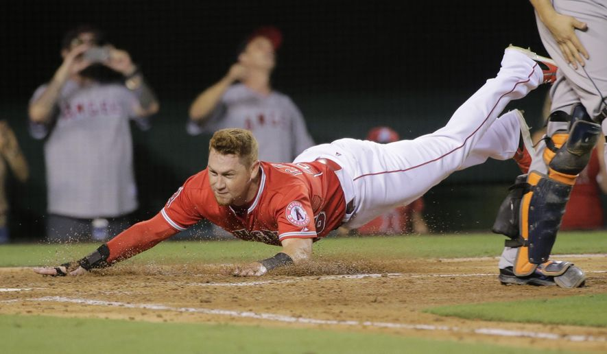 Los Angeles Angels' Kole Calhoun slides into home plate to score on a double by Mike Trout during the fourth inning of a baseball game against the Houston Astros on Friday, Sept. 12, 2014, in Anaheim, Calif. (AP Photo/Jae C. Hong)