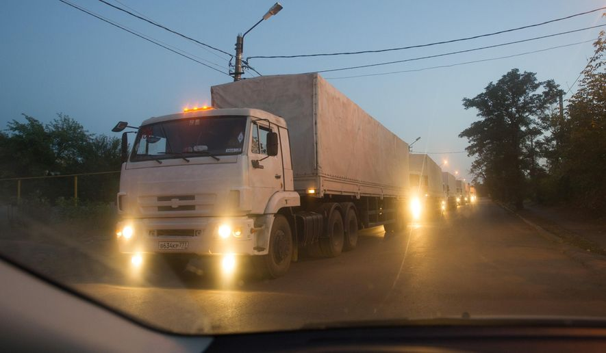 Russian trucks, carrying humanitarian aid for eastern Ukraine, are driven to a border check point in the town of Donetsk, Rostov-on-Don region, Russia, early Saturday, Sept. 13, 2014.  The second convoy of Russian trucks that entered rebel-held territory in eastern Ukraine earlier Saturday, is reportedly filled with almost 2,000 tons of humanitarian aid. (AP Photo)
