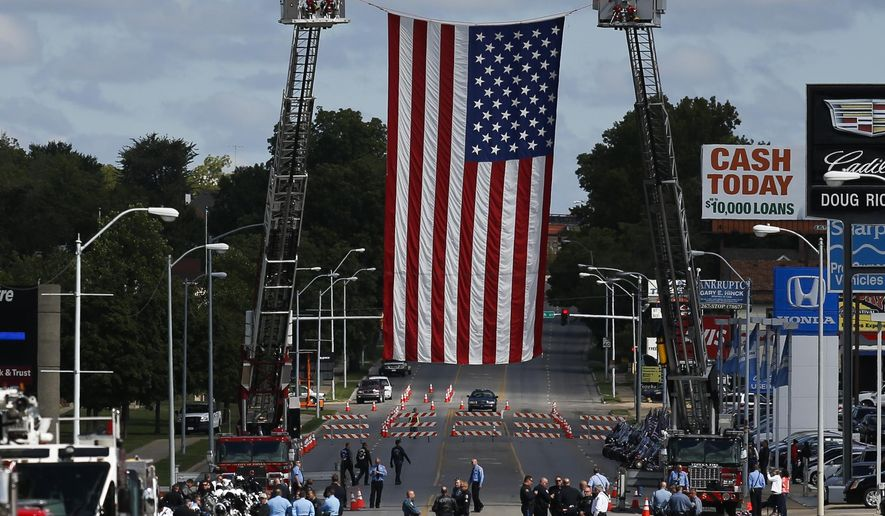 A 30x50-foot garrison flag was suspended by two Topeka Fire Department ladder trucks for Cpl. Jason Harwood's funeral Saturday, Sept. 13, 2014, in Topeka, Kan. (AP Photo/The Topeka Capital Journal, Anthony S. Bush)