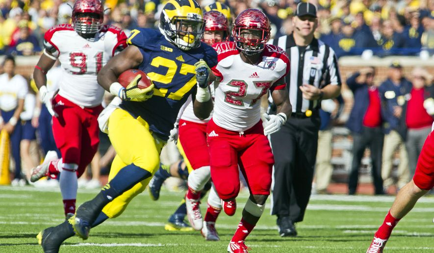 Michigan running back Derrick Green, front left, defended by Miami (Ohio) defensive back Jarrell Jones, front right, rushes on a carry in the second quarter of an NCAA college football game in Ann Arbor, Mich., Saturday, Sept. 13, 2014. (AP Photo/Tony Ding)